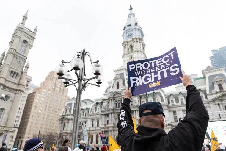 """A Working People's Day of Action rally attendee holds up a sign that reads """"Protect Workers' Rights"""" in Thomas Paine Plaza on Saturday morning, February 24, 2018. SYDNEY SCHAEFER / Staff Photographer"""