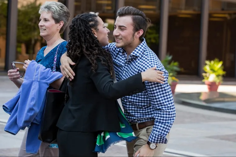 Ria Mar (center), senior staff attorney with the ACLU, hugs Aidan DeStefano, a transgender student who recently graduated from Boyertown Area Senior High School, outside federal court in Philadelphia on Thursday.  Aidan DeStefano's mother, Melissa DeStefano, is at left.