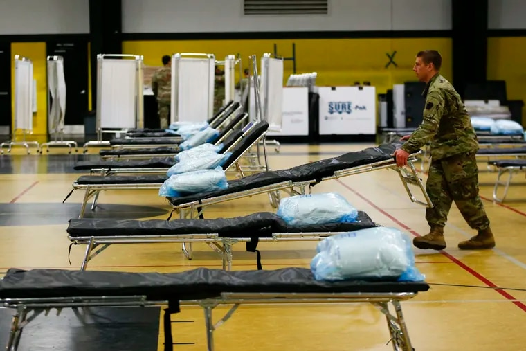 A member of the 103rd Brigade Engineer Battalion National Guard adjust a cot bed in the gymnasium at the Glen Mills School.  FEMA and National Guard members will assemble medical equipment and beds in the field hospital to make room for coronavirus patients elsewhere.