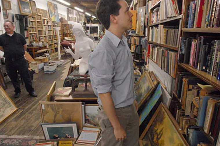 At Jules Goldman Books and Antiques in Old City, above, Lee West scans the titles. At left in the background is Jules Goldman himself. (APRIL SAUL / Staff Photographer)