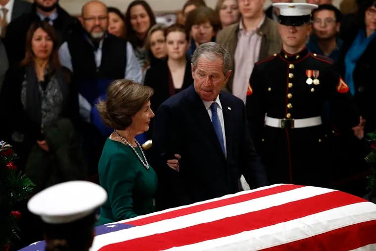 Former President George W. Bush glances toward former first lady Laura Bush as they pause in front of the flag-draped casket of former President George H.W. Bush as he lies in state in the Capitol Rotunda in Washington, Tuesday, Dec. 4, 2018.
