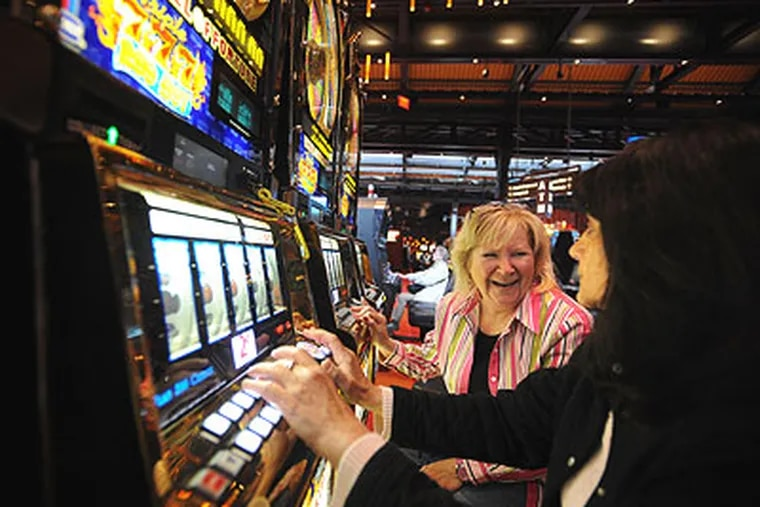 At the Sands Casino Resort in Bethlehem last month, Kathy Frey of Allentown (left), tells her friend Angela Brazzo of Hellertown, about her wins on the slots. Slow business prompted the casino to lay off 80 workers Friday. (Sharon Gekoski-Kimmel / Staff Photographer)