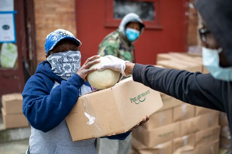 Joseph Hill, 25, of West Philadelphia, hands out cantaloupe along with the boxes of packaged food from Philabundance to a local in the area at the corner of 59th Street and Lansdowne Avenue on April 23, 2020. One box is provided per household and contains non-perishable items on Mondays and fresh produce on Thursdays.