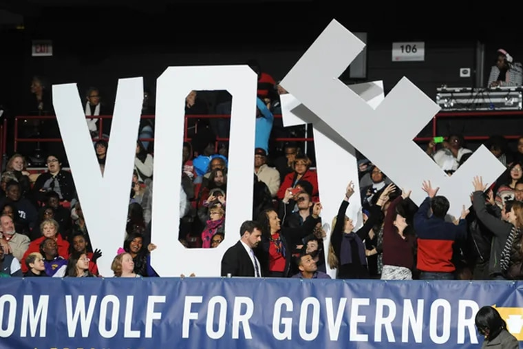 Getting the letters in place encouraging people to vote at a campaign rally for Tom Wolf, Democratic candidate for governor of Pennsylvania, at Temple University in which President Obama appeared and gave remarks Nov. 2, 2014. (CLEM MURRAY/Staff Photographer)
