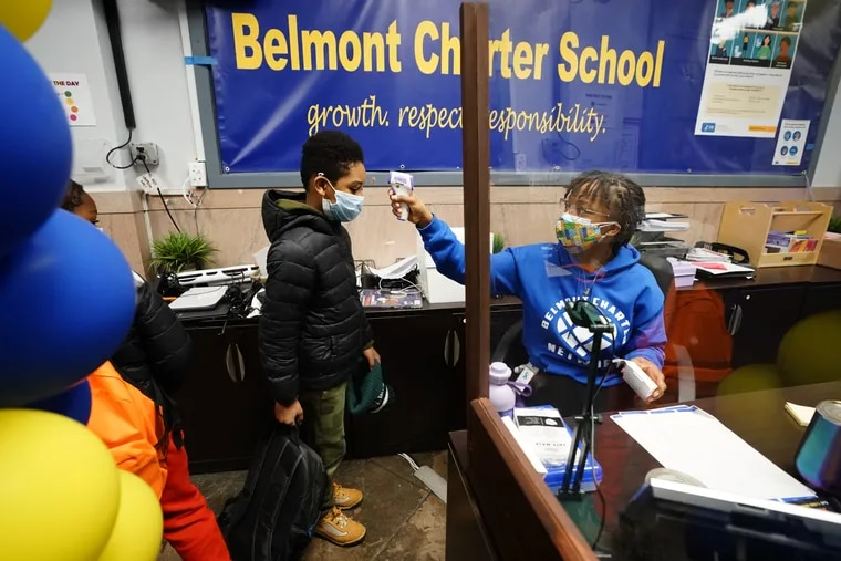 Student Lamir Smith (left) has his temperature taken by Admin Assistant Lakita Williams at Belmont Charter School in February.