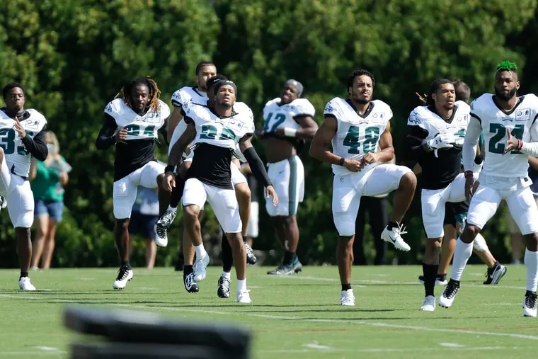 Eagles defensive backs run during training-camp drills at the NovaCare Complex in South Philadelphia on Monday.