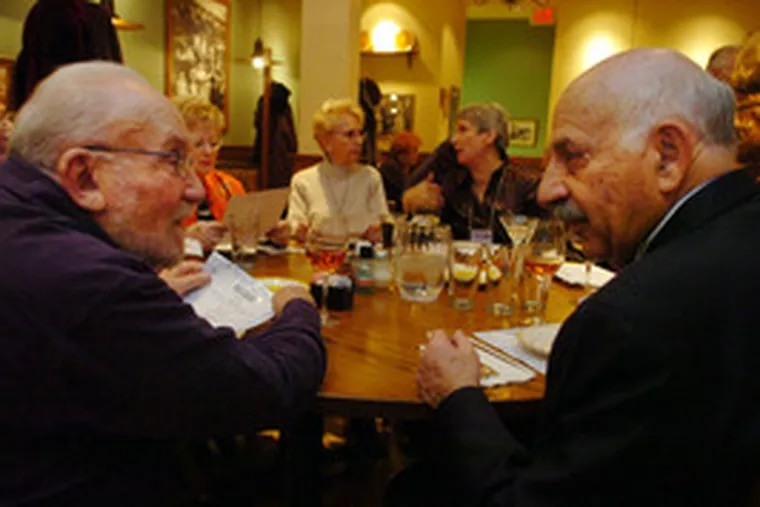 Joseph Knepler (left) of Swarthmore and Bob Marx of Cherry Hill introduce themselves. A sub-group gets together to dine out.