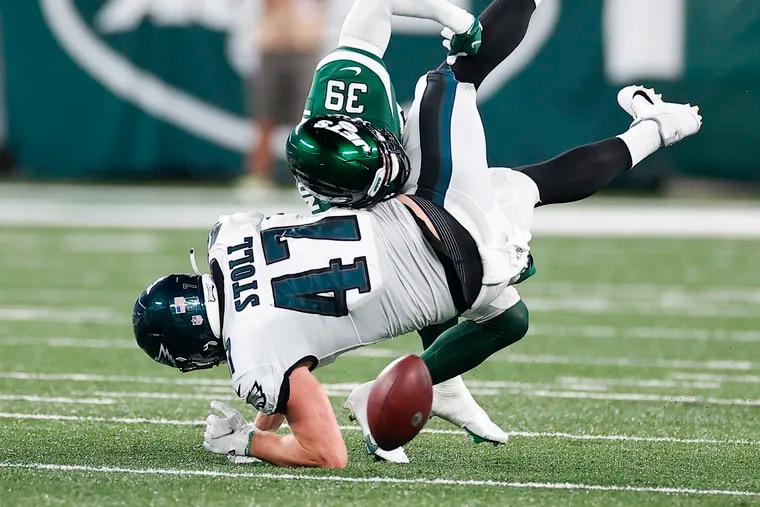 Eagles tight end Jack Stoll takes a hit from Jets defensive back Bennett Jackson after dropping a pass during a preseason game last month.