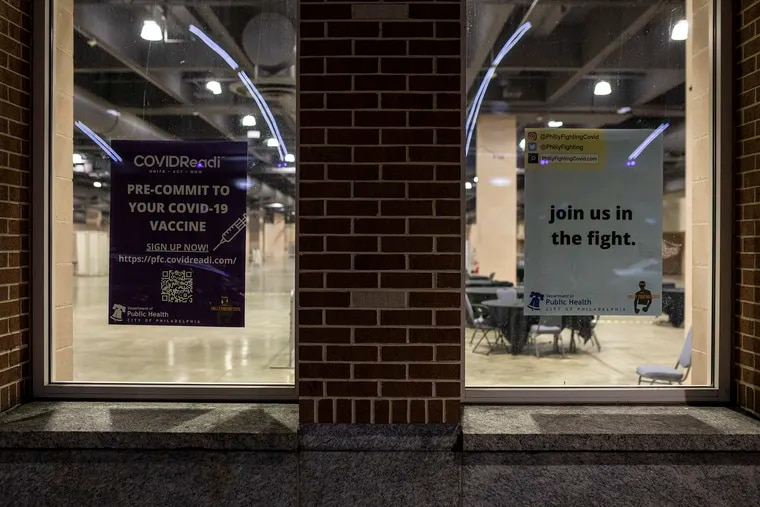 Posters from Philly Fighting COVID are displayed on the windows of the Philadelphia Convention Center where stations are made for a COVID-19 vaccine clinic. The city has ended partnership with Philly Fighting COVID organization.