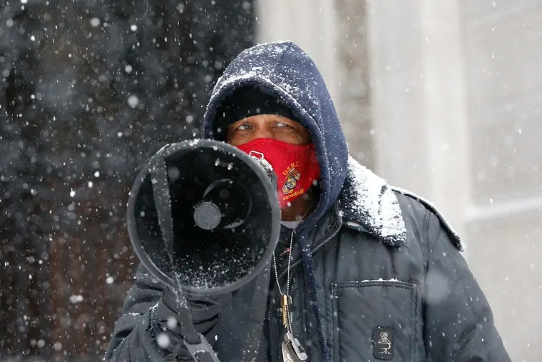 Jamal Johnson of Germantown talks into his bullhorn as snow falls at City Hall on Monday, February 1, 2021.  Johnson has embarked on a one-man hunger strike in an attempt to call attention to gun violence and specifically a resolution he and others want Mayor Kenney to sign.