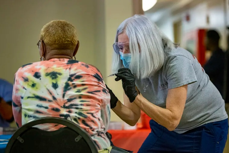 Barb Little, a registered nurse and instructor with Temple University, injects a patient with the Pfizer vaccine. The Philadelphia Housing Authority and Temple University College of Public Health brought the mobile vaccination program to Emlen Arms Apartments on Monday.