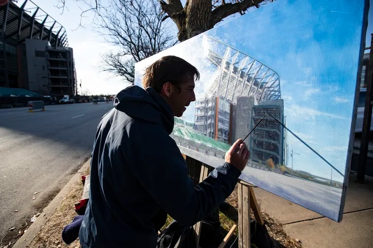 Damian Smith puts the finishing touches on his painting of Lincoln Financial Field.