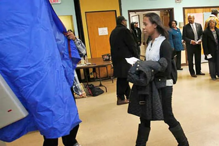 """A voter carries her ballot at the John C. Anderson Cultural Center polling place on Tuesday. The """"gender gap"""" may have contributed to Obama's success. ALEJANDRO A. ALVAREZ Staff Photographer"""