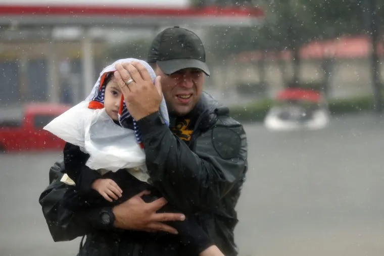 Sgt. Chad Watts of the Louisiana Department of Wildlife and Fisheries holds Madelyn Nguyen, 2, after he rescued her and her family by boat from floodwaters of  in Houston.