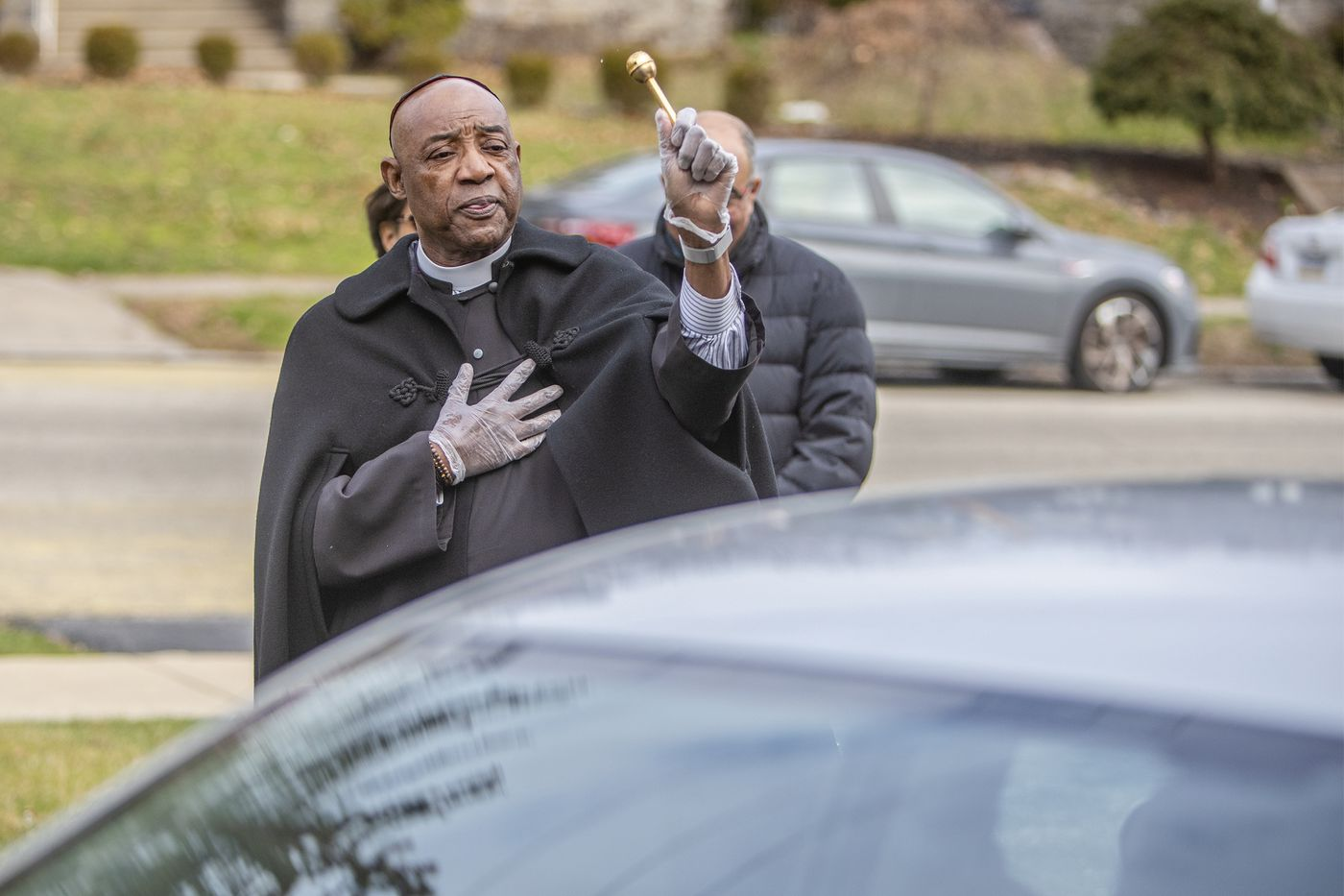 As a congregant of St. Thomas Church drives away after receiving a communion wafer, the Rev. Gerald Collins offers a blessing and sprinkle of holy water.