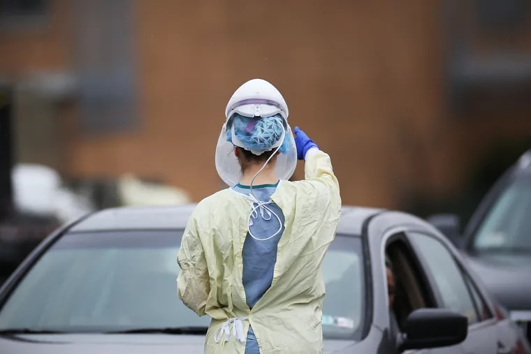 """A medical worker prepares to collect samples from individuals who signed up for """"drive-through testing"""" for the coronavirus at a Penn Medicine site in West Philadelphia on March 17."""