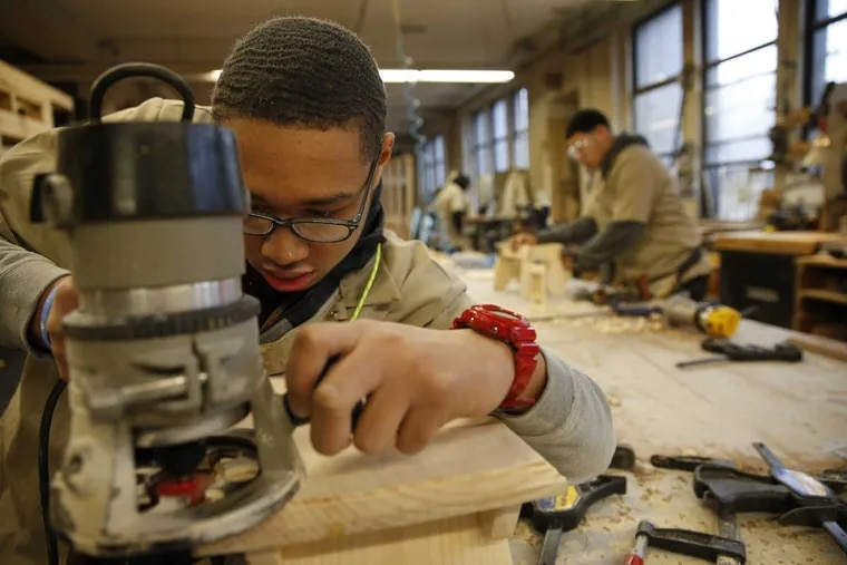 Christopher White, 16, a sophomore, works on a foot stool in the woodworking class at Mercy Career & Technical High School.