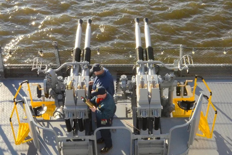 Navy Veteran, Ken Kerch, left, and volunteer, Dan Lawler, clean the Quad 40 gun, Thursday, Dec. 7, 2017., minutes after firing shots from the Battleship New Jersey. The event on board the battleship marked two anniversaries — of the attack on Pearl Harbor and the launch of the ship 75 years ago on this date.