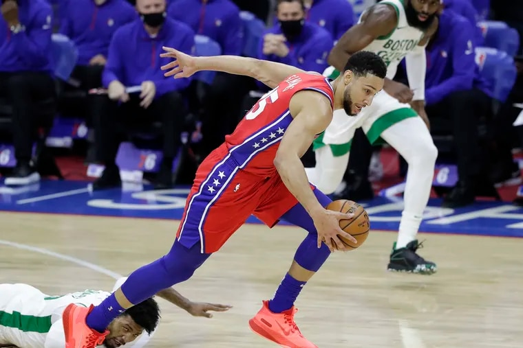 Sixers guard Ben Simmons steals the basketball from Boston Celtics guard Marcus Smart (on the floor) and guard Jaylen Brown during the first quarter on Friday.