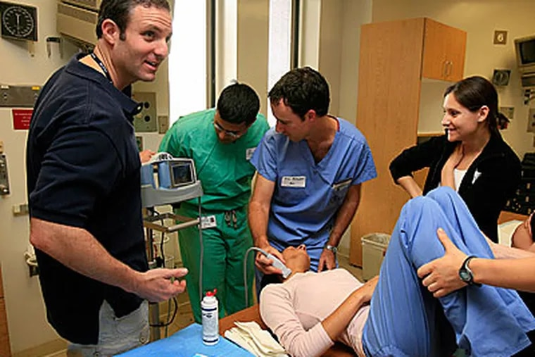 Dr. Roger Band, Univ. Penn Emergency Medicine (left) teaches med students how to use a portable ultrasound machine for central venous catheter procedure. (Akira Suwa / Staff Photographer )