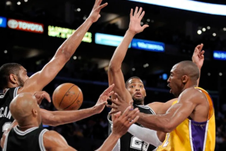 The Lakers' Kobe Bryant goes against Spurs defenders (from right) Robert Horry, Tim Duncan and Bruce Bowen. Bryant scored 25 points in the second half of the 89-85 win in Los Angeles.
