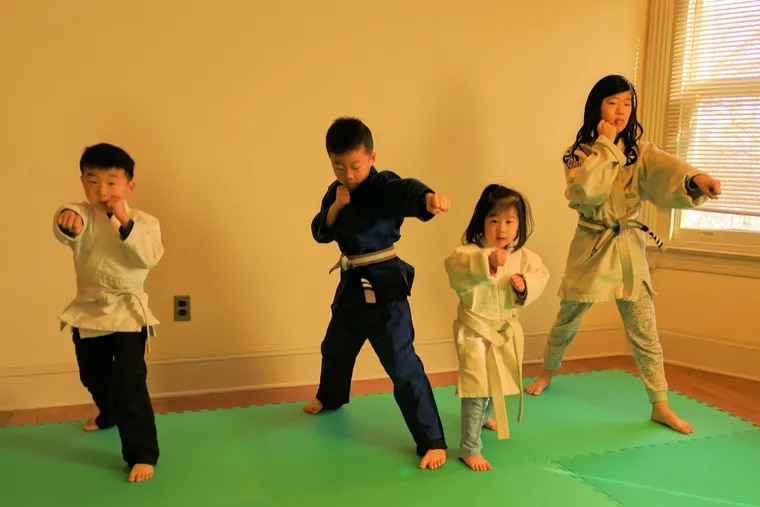 Councilman David Oh's children, Daniel, 7, Joshua, 8, Sarah, 4, and Hannah, 11, practice martial arts in their Southwest Philadelphia home. Oh said he was wrongfully investigated for suspected child abuse after Joshua suffered an accidental injury during a morning practice.