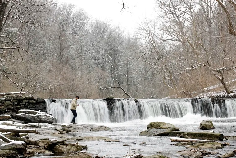 A hiker steps upon rocks in the Wissahickon Creek after a winter storm in Philadelphia, Monday, Feb. 11, 2019.