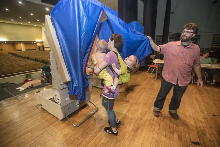 Vera Dugan, 18 months, right, holds on tight to Bridget Huffman, center, as she holds her son Drew Huffman, 20 months, left, as they all go into the voting booth together, on the stage of the auditorium of South Philadelphia High School on May 15, 2018. Nazim Karacaa, right, holds open the blue curtain so Huffman and her brood can enter to vote in the primary election in the 39th District in South Philadelphia.