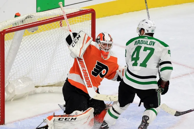 Brian Elliott, left, stops a shot by Alexander Radulov in overtime, helping the Flyers post a 2-1 win Saturday.