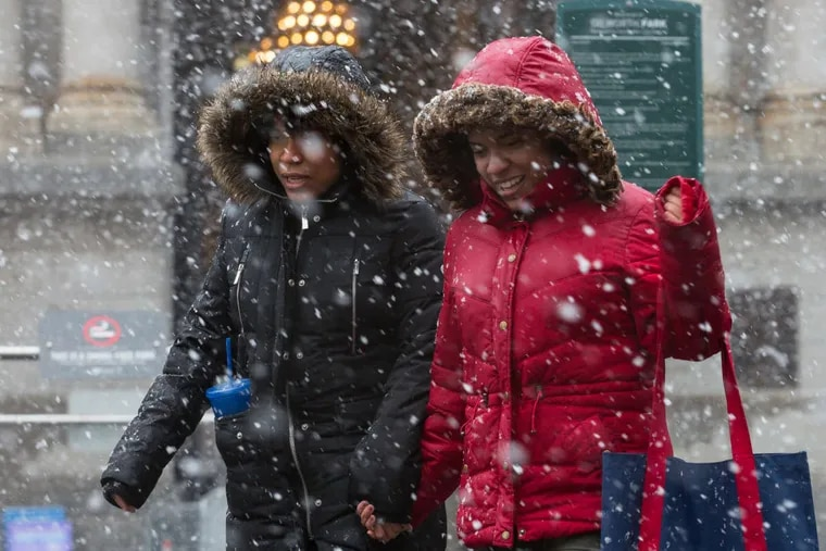 Twin sisters Amber Davis (left) and Alysia Davis make their way through Friday's storm in front of City Hall in Philadelphia.