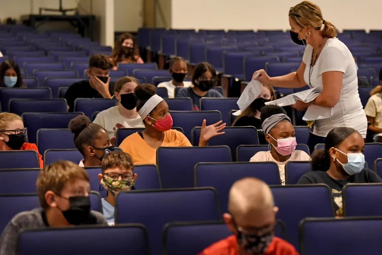 School nurse Kathy Dreger hands out paperwork to junior high school students as they attend an orientation at Woodbury High School on Tuesday. When New Jersey students return to school next week, they face a mask mandate.