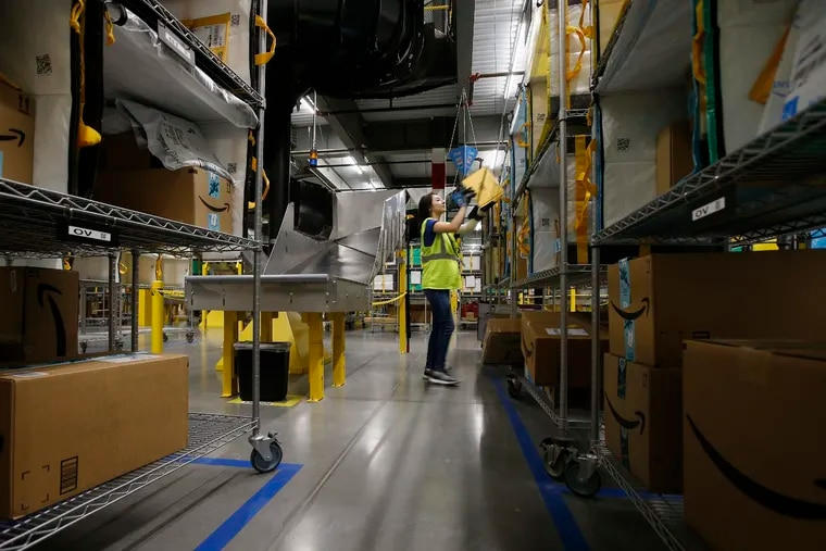 In this Dec. 17, 2019, photo Jocelyn Nieto stows packages into special containers after Amazon robots deliver separated packages by zip code at an Amazon warehouse facility in Goodyear, Ariz. Companies that order, pack and ship goods are moving up seasonal hiring earlier in the year and converting gig positions to full-time roles at a faster clip than before. (AP Photo/Ross D. Franklin)
