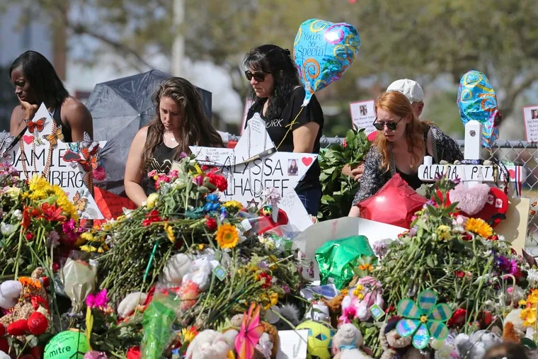 In this Feb. 25, 2018 photo, mourners bring flowers as they pay tribute at a memorial for the victims of the shooting at Marjory Stoneman Douglas High School, in Parkland, Fla. The community is focusing on suicide prevention programs after two survivors of the Florida high school massacre there killed themselves this month.