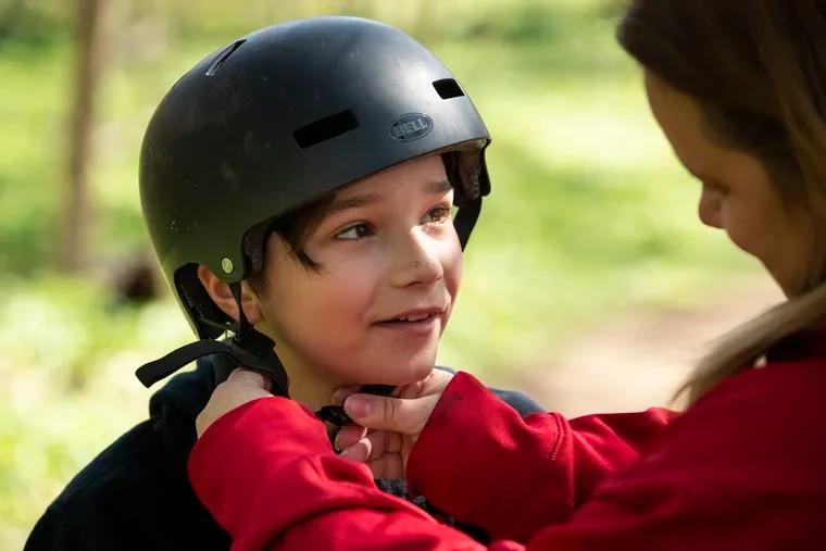 Karen Nudy Pecora adjusts the helmet on her son Dominick Pecora, 11, in the woods near their home.