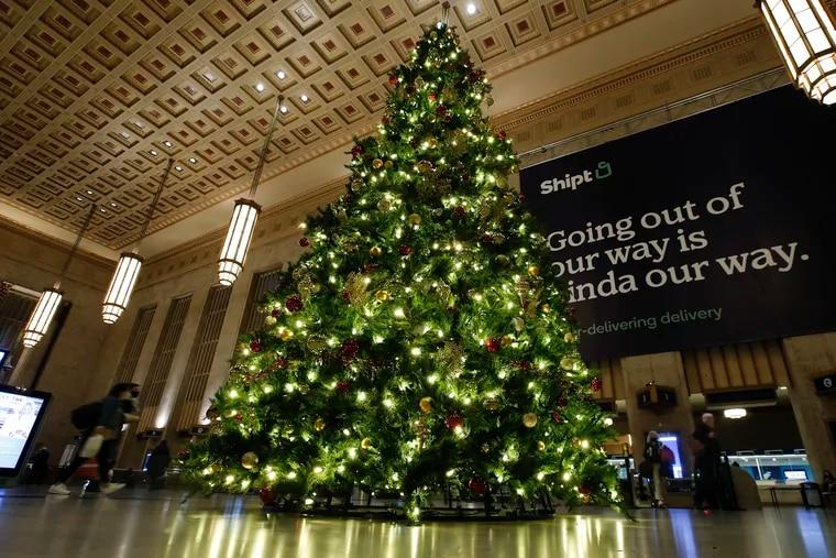 Travelers walk near the Christmas Tree at 30th Street Station.