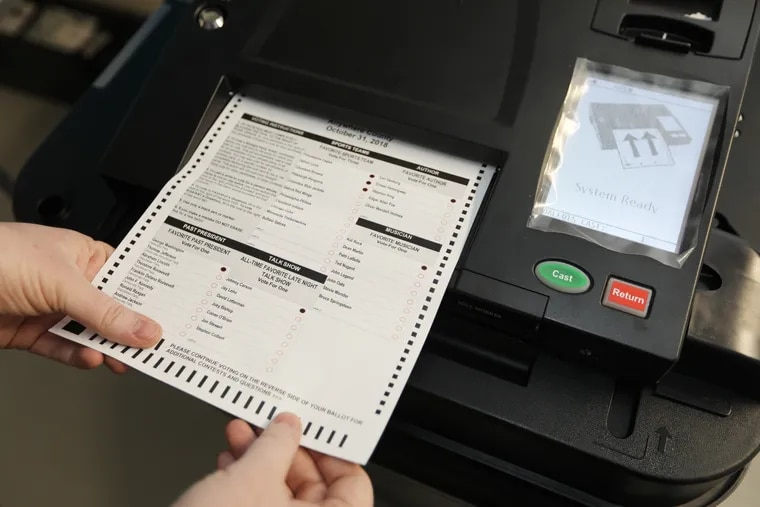 Mark Macekura from the election board feeds a paper ballet into a new scanner. Montgomery County has received new voting machines it will begin using in the primary this May.