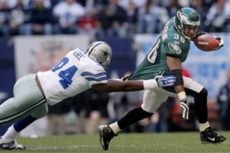 Brian Westbrook can't shake loose from DeMarcus Ware in the first quarter. Westbrook rushed for 81 yards, 58 in the second half.