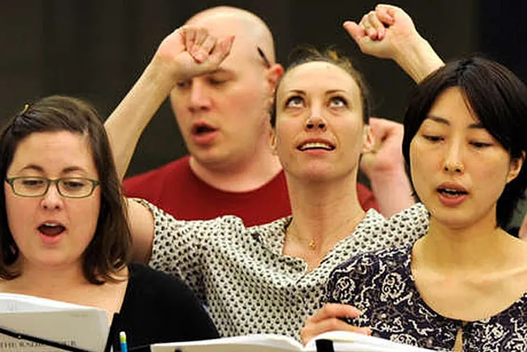"""In the midst of the Philadelphia Singers, dancer Elizabeth Coker (center, looking up) rehearses her silent role as Nora in Jake Heggie's choral opera """"The Radio Hour.""""  (Tom Gralish/Staff Photographer)"""