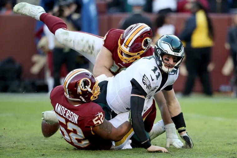Eagles quarterback Carson Wentz fumbles the football as he is hit by Washington's Ryan Anderson, left, and Matt Ioannidis, center, in the Philadelphia Eagles win 37-27 over the Washington Redskins at FedEx Field in Landover, MD on December 15, 2019.