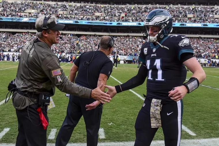 Eagles quarterback Carson Wentz gets congratulated by head coach Dough Pederson after throwing a touchdown pass to Alshon Jeffrey against the Broncos on Sunday.
