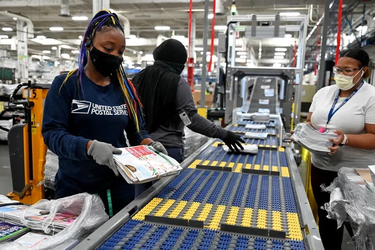 Postal workers (from left) Terry Bynum, Ranesha White, and Dymya Walker load packages onto the new package sorting machine at the Philadelphia mail processing facility.