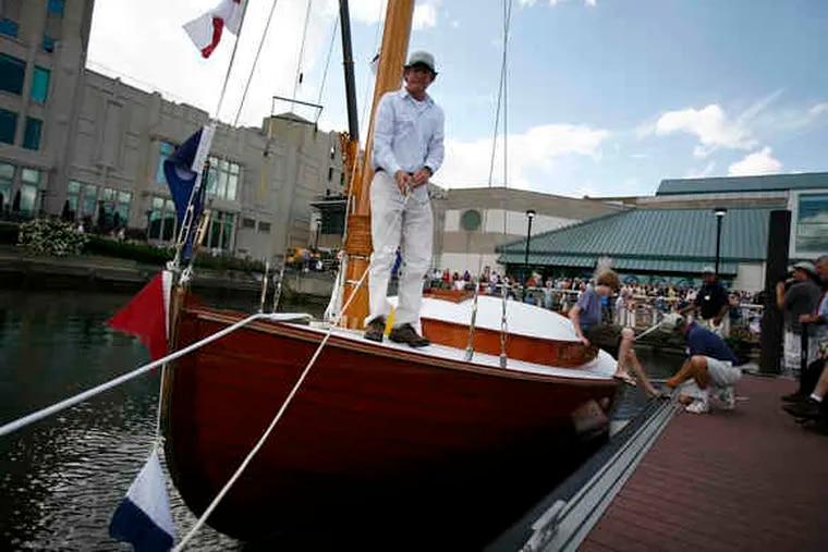 John Brady, who oversaw the new Silent Maid's construction, helps guide it to a dock. The catboat was lowered into the water after being christened at Independence Seaport Museum.