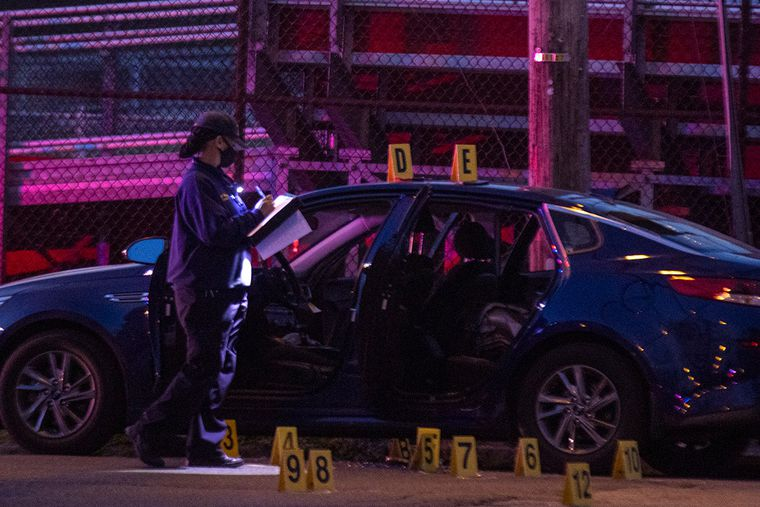 Philadelphia crime scene unit laying down evidence markers after gunfire left 24-year-old man dead and officer wounded at 15th Street and West Somerville Avenue in North Philadelphia on Wednesday, April 7, 2021.