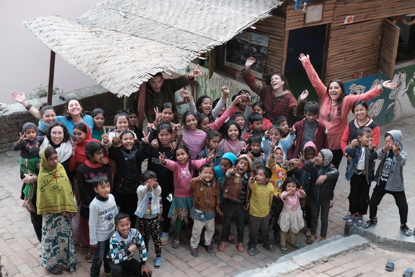 In 2018, the Happy Kids Center underwent major renovations and beautification at the hands of several of the center's volunteers, pictured here with the children.This photo was taken just before the project began, as a remembrance of the original center.