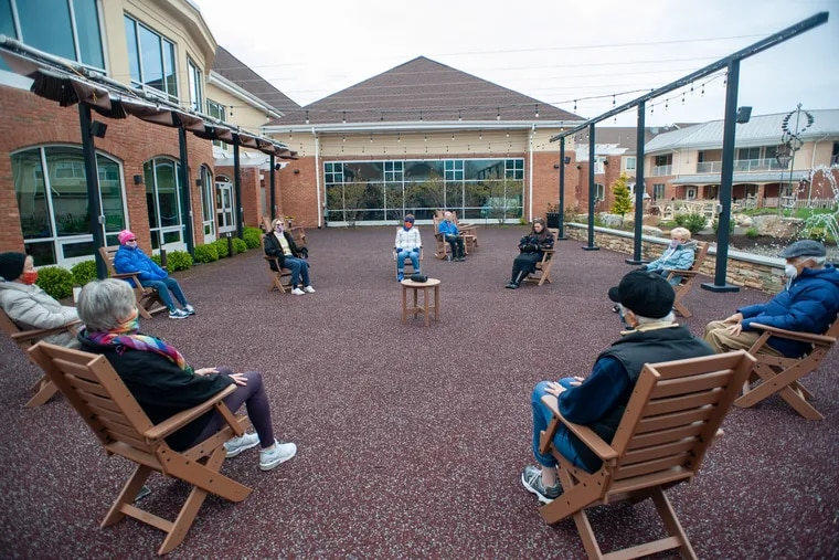 A group of residents meditate outdoors in April at Meadowood, a senior living facility in Worcester.  Such activities are an effort to reduce isolation.