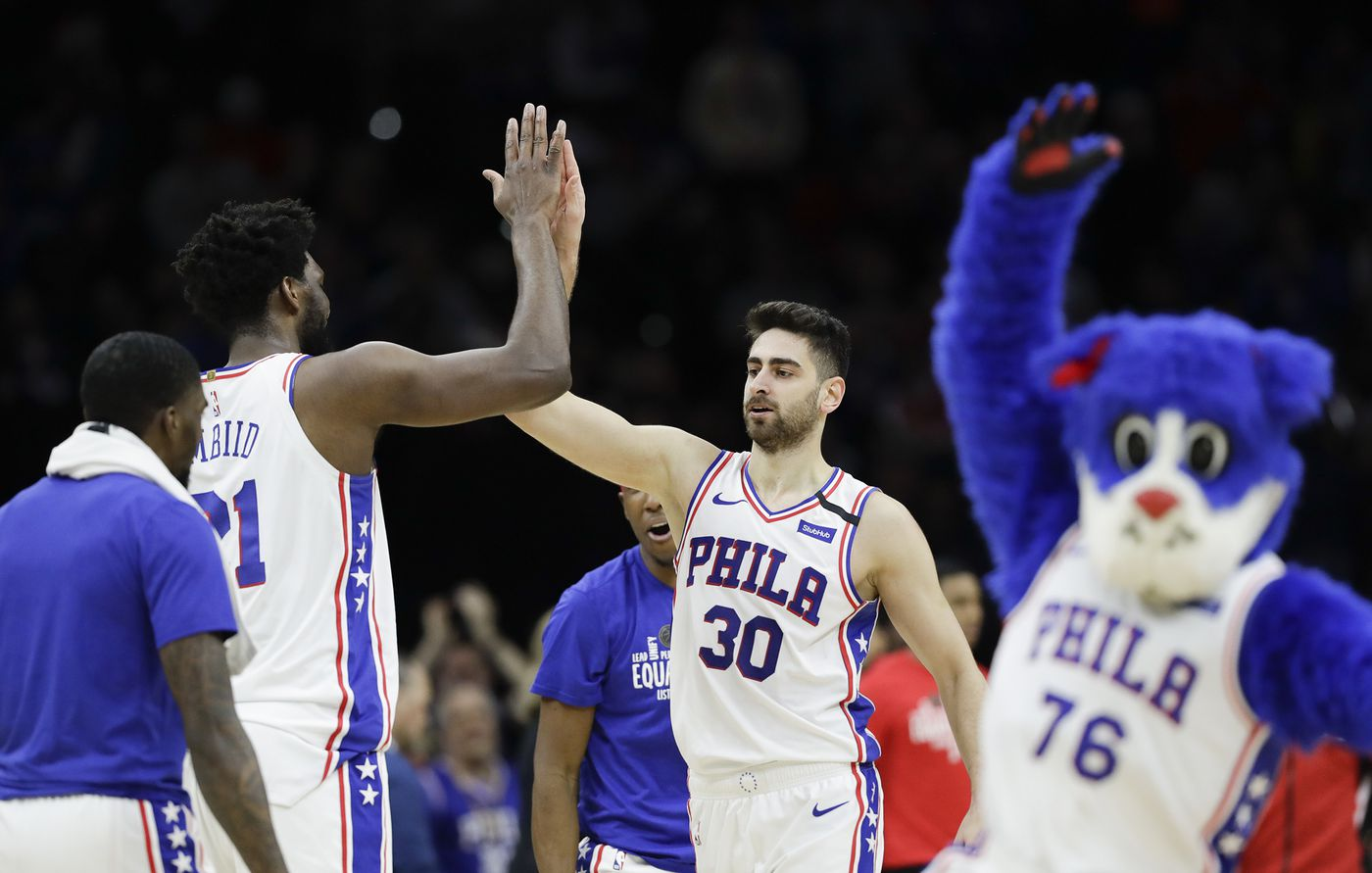 Sixers guard Furkan Korkmaz high-fives teammate center Joel Embiid after Kormaz dunked the basketball against the Chicago Bulls on Sunday, February 9, 2020 in Philadelphia.