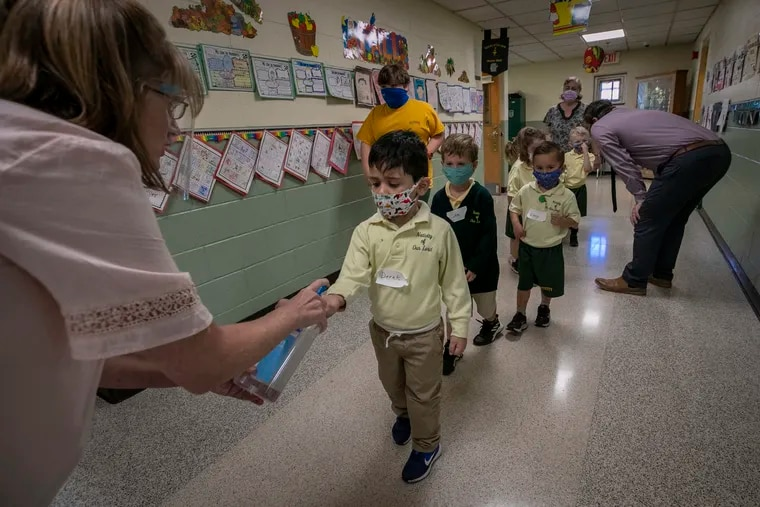 Teacher Megan DiToro pumps hand sanitizer into the hands of preschool students as they move around Nativity of Our Lord, a Catholic school in Warminster. The school offers full-time, in-person education with extensive COVID-19 precautions.