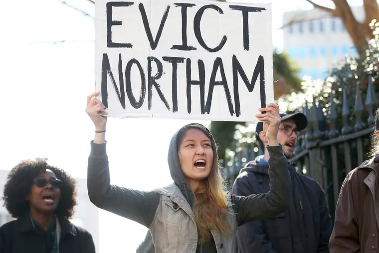 Geraldine Mabagos, of Richmond, Va., holds a sign during a protest in Richmond on Monday, Feb. 4, 2019, calling for Gov. Ralph Northam to resign. Northam has rebuffed widespread calls for his resignation after a racist photo surfaced Friday in his 1984 medical school yearbook page.  (Shelby Lum / Richmond Times-Dispatch via AP)