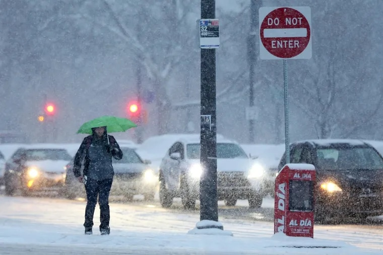 A pedestrian braves the snow with an umbrella near 23rd and Spring Garden streets as snow falls on Friday, Dec. 15, 2017. TIM TAI / Staff Photographer