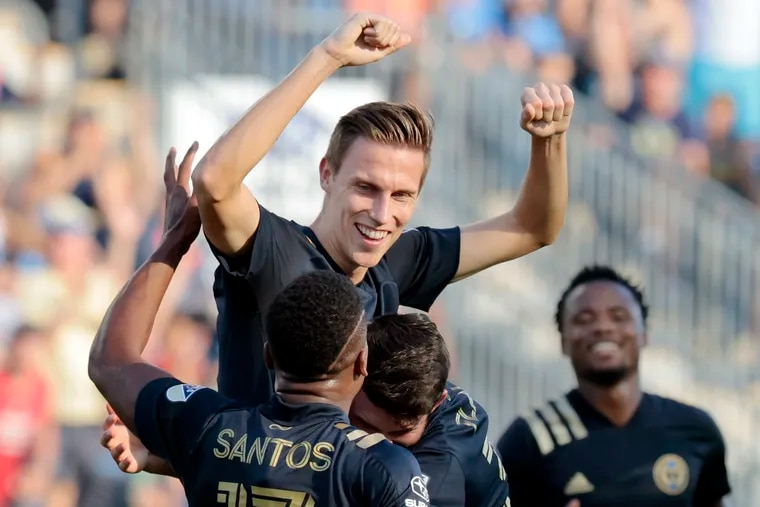 Jack Elliott, center, celebrates with teammates after scoring on a free kick for the Union's opening goal.